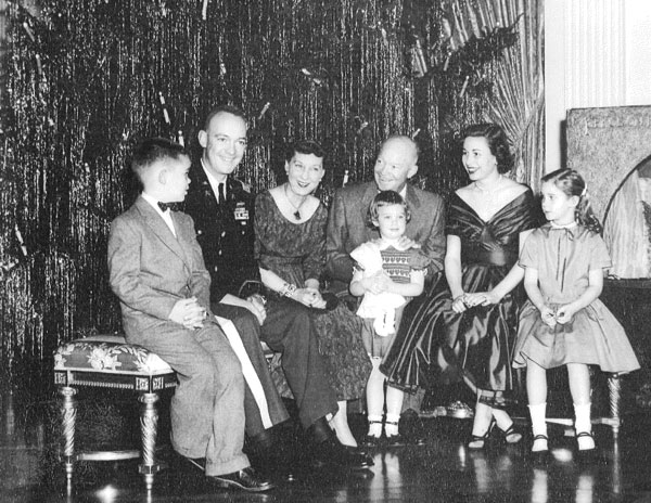 President Dwight D. Eisenhower and family, Christmas 1955. From left to right, David Eisenhower, General John S.D. Eisenhower, First Lady Mamie Eisenhower, Susan Eisenhower, President Dwight Eisenhower, Barbara Thompson Eisenhower Foltz, and Anne Eisenhower (Mary Jean, the youngest sibling, is not pictured)